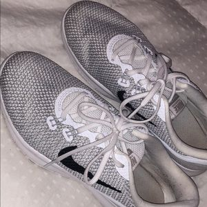 Silver and white Nike tennis shoes